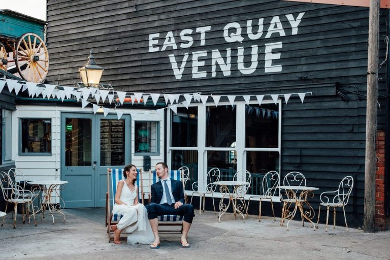 bride and groom sitting on deckchairs out the front of the east quay wedding whitstable kent