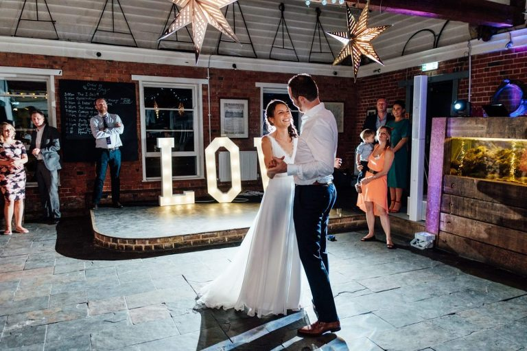 bride and groom smiling during first dance at their east quay whitstable wedding in kent